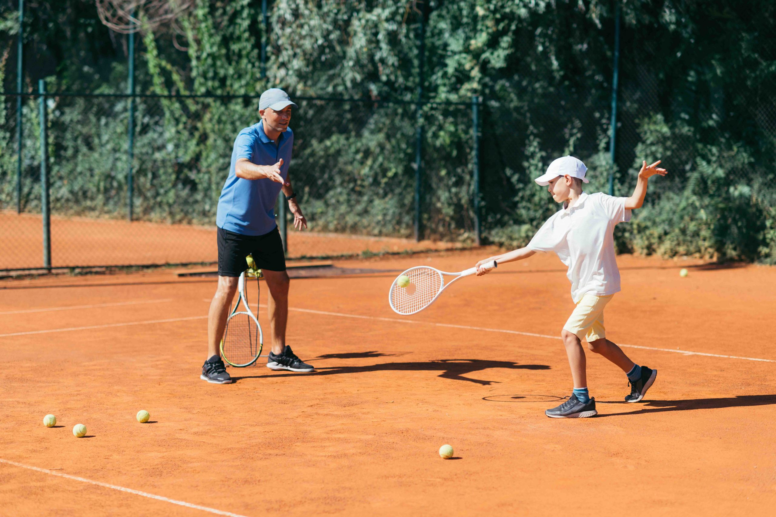 Tennis Instructor with Boy Having a Tennis Lesson on Clay Court.